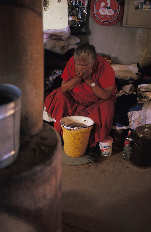"""Washing - Katherine Smith, who lives 22 miles from the nearest paved road, washes herself from a bucket that she heats on her wood-burning stove.  Smith, like other resistors, has rejected relocation with its modern conveniences of running water, electricty - and as Smith puts it - """"a highway to the doorway."""""""