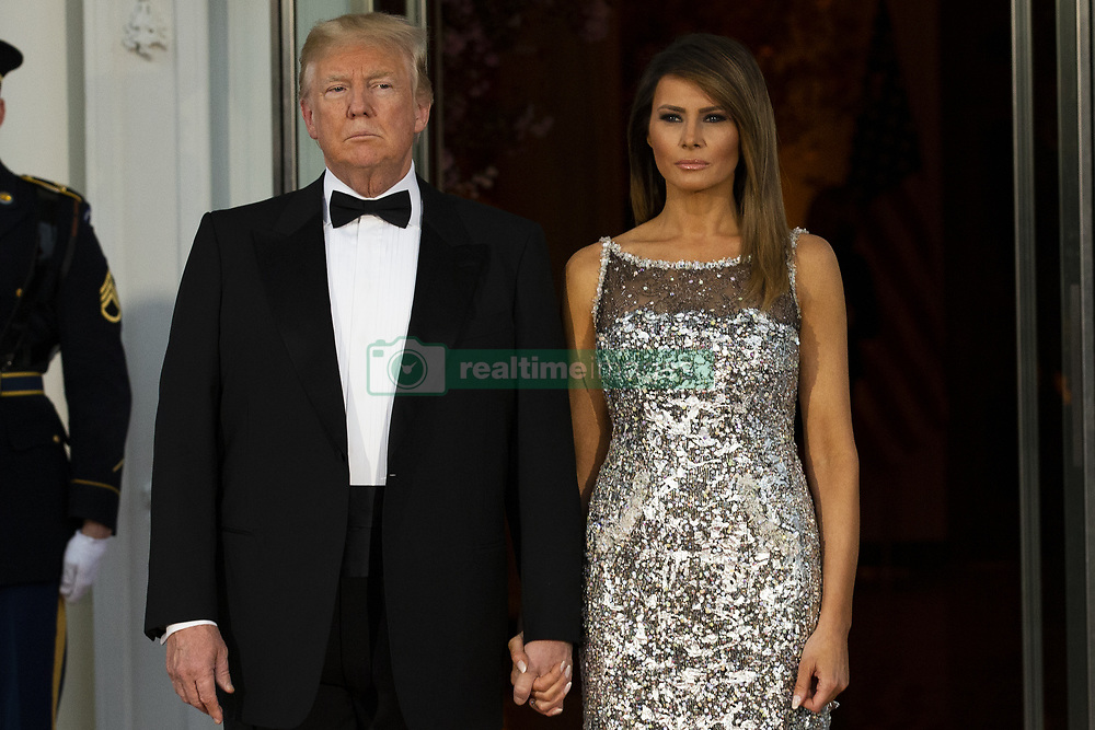 April 24, 2018 - Washington, District of Columbia, U.S. - President DONALD TRUMP and first lady MELANIA TRUMP emerge from the White House as the await the arrival of French President Emmanuel Macron and first lady of France Brigette Macron prior to the State Dinner during the French State Visit to the United States. (Credit Image: © Alex Edelman/CNP via ZUMA Wire)