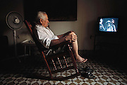 Euripedes Costa watches television during a rare peaceful moment when his grandchildren are not running through the house or playing their music loudly. Marianao district of Havana, Cuba. From coverage of revisit to Material World Project family in Cuba, 2001.