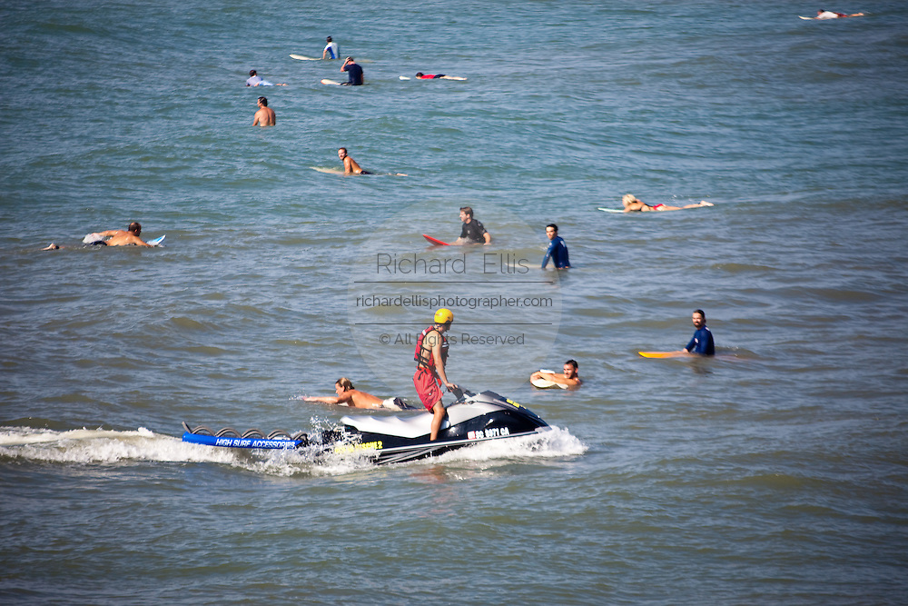 Surf patrol rides along in a jet ski as surfers gather to take advantage of the ocean swell generated by a passing hurricane along the South Carolina coast in Folly Beach, SC