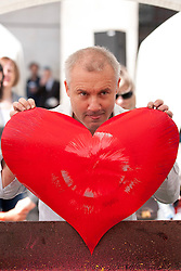© Licensed to London News Pictures. 14/06/2012. LONDON, UK. Artist Damien Hirst holds a heart created using his spinning technique at a public art workshop in Covent Garden, London, today (14/06/12). In celebration of Damien Hirst's current exhibition at the Tate Modern, the artist held a pubic art event giving British School children the chance to create their own versions of his iconic spin paintings. Photo credit: Matt Cetti-Roberts/LNP