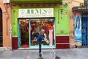 Woman mopping the street outside Jueves vintage clothes shop in Barrio Macarena, Seville, Spain