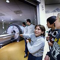 Nederland, Amsterdam , 10 november 2013.<br /> Op zondag 10 november wordt er een ochtend georganiseerd in VUmc van de Kinderuniversiteit. 14 kinderen komen dan lessen volgen in neurowetenschappen en nemen bijv ook een kijkje bij de MRI.<br /> Op de foto: Kinderen testen de kracht van het magnetisch veld door het trekken aan een touw waar een stuk metaal aan vast zit zwevend in de ruimte waar de MRI scanner staat.<br /> Foto:Jean-Pierre Jans