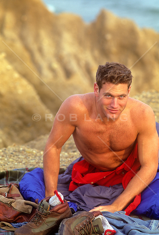 very sexy shirtless man sitting up with camping gear around him in Montauk, NY
