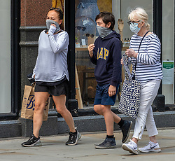 © Licensed to London News Pictures. 23/07/2020. London, UK. A family shopping in Chelsea wear masks while shopping on the Kings Road before it becomes compulsory in shops in England tomorrow. Face masks will be compulsory in shops, takeaway cafes and supermarkets from 24th July and enforced by the Police, with anyone who fails to wear one liable to a £100 fine. Photo credit: Alex Lentati/LNP