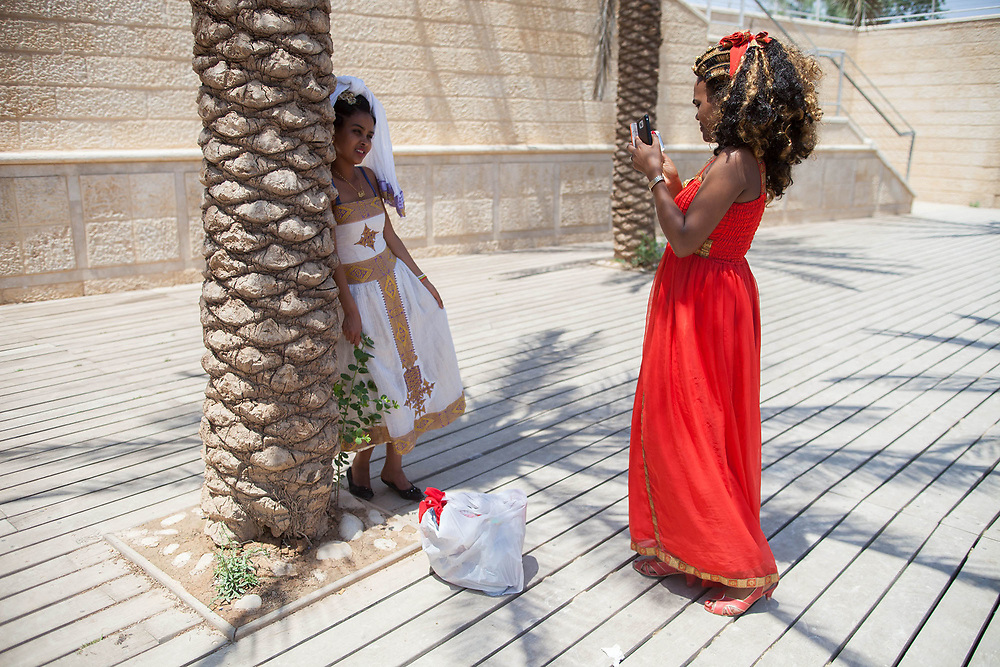A Christian pilgrim is taking a photo of a companion dressed in traditional clothing at the Qasr el Yahud or Castle of the Jews baptism site in the Jordan River Valley.