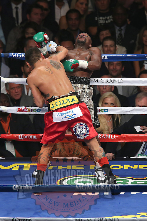 LAS VEGAS, NV - SEPTEMBER 13: (R-L) Floyd Mayweather Jr. falls back after a punch by Marcos Maidana during their WBC/WBA welterweight title fight at the MGM Grand Garden Arena on September 13, 2014 in Las Vegas, Nevada. (Photo by Alex Menendez/Getty Images) *** Local Caption *** Floyd Mayweather Jr; Marcos Maidana