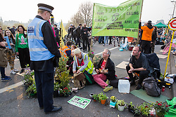 London, UK. 17th April 2019. Climate change activists from Extinction Rebellion, who continue to occupy Waterloo Bridge on the third day of International Rebellion activities, speak to a police officer.