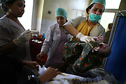 Dr. Zahira, at right, carries the baby shortly after a pregnant woman gave a birth at Faizabad Provincial Hospital in Badakshan province, Afghanistan, Wednesday, May 9, 2007. Faizabad Hospital's maternity unit has the most advanced facility in Badakshan. However, it also suffers from lack of facilities and staff especially female doctors. Afghanistan has the second highest maternal mortality rate in the world only after Sierra Leone. An astonishing number of 25,000 women die from obstetric causes per year, or 1 woman dies every 27 minutes. A UN report released in 2000 indicates that the national MMR in Afghanistan was 1,900 per 100,000 live births, whereas it was 17 in the United States. Ragh district in Badakshan province showed the highest mortality risk ever recorded in human history, with 64% - more than half of women - of reproductive age died during 1999 and 2002. The causes of deaths were analyzed mainly in two parts: direct and indirect. Direct causes include haemorrhage, obstructed labour, cardiomyopathy, sepsis, obstetric embolism, and pregrancy-induced hypertension; and the indirect causes were tuberculosis, malaria, and obstetric tetanus. Geographical and economical factors also contribute to high mortality in a place like Badakshan where most people have limited access to transportation thus making it harder for women to reach proper health care centers.