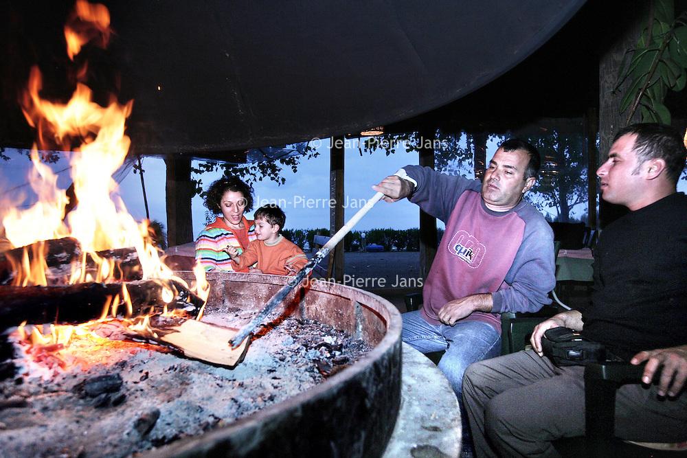 Turkije,Cirali, Antalya ,27 november 2007..familie en eigenaar van 1 van de weinige strandtentjes van het Zuid Turkse kustplaatsje Cirali warmt zich op aan het vuur bij de open haard aan het einde van het seizoen...Foto:Jean-Pierre Jans