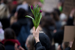 © Licensed to London News Pictures. 14/03/2021. London, UK. A protestor holds aloft flowers outside New Scotland Yard in London during a demonstration, organised by Sisters Uncut, against the actions of the police force at a vigil for murdered Sarah Everard yesterday evening. There have been calls for Met Chief Cressida Dick to resign following yesterday's scenes, when police dragged women away from a bandstand as thousands gathered in Clapham, South London. Photo credit: Ben Cawthra/LNP