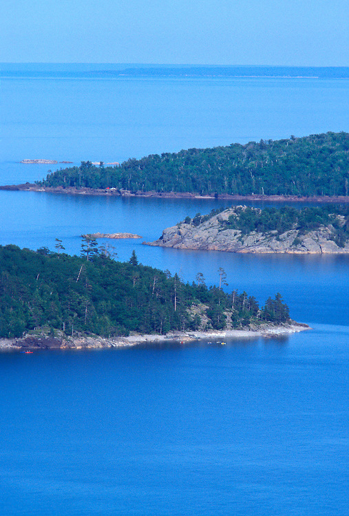 Kayakers paddle around Partridge Island, left, Middle Island, center, and Presque Isle Park, rear, are seen from the top of Sugarloaf Mountain in Marquette, Mich.