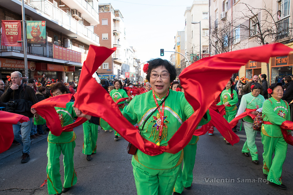 Madrid, Spain. 18th February, 2018. Woman wearing a green costume with a red scarf dancing during the Chinese New Year parade in Madrid. © Valentin Sama-Rojo