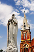 Granite statue of the Virgin Mary and one of the towers of the Gothic Revival styled Saigon Notre-Dame Cathedral Basilica. The cathedral was built between 1863 and 1880, the statue was installed in 1959. Ho Chi Minh City (Saigon), Vietnam
