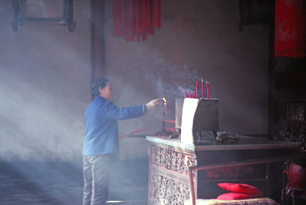 Wuhan 1986: a woman burning incense in a  temple just re-opening.