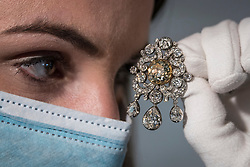 "© Licensed to London News Pictures. 19/03/2021. LONDON, UK. A staff member views the ""Banks diamond' pendant/brooch, late 18th century and later, which <br /> commemorates Sir Joseph Banks (est. £40,000-60,000).  Preview of the upcoming sale of property from the collection of the Patricia Knatchbull, 2nd Countess Mountbatten of Burma.  Over 350 lots spanning jewellery, furniture, paintings, sculpture, books, silver, ceramics & objets d'art are to be auctioned on 24 March at Sotheby's New Bond Street galleries.  Photo credit: Stephen Chung/LNP"