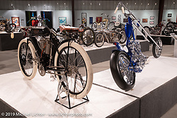 "1908 Indian Twin ""Torpedo Tank"" 61 cubic inch board track racer from the Jill and John Parham Collection (L) and Vintage Technologies Hawke Lawshe's custom 1946 Harley-Davidson open rocker Knucklehead on display in the   on view in the What's the Skinny Exhibition (2019 iteration of the Motorcycles as Art annual series) at the Sturgis Buffalo Chip during the Sturgis Black Hills Motorcycle Rally. SD, USA. Friday, August 9, 2019. Photography ©2019 Michael Lichter."