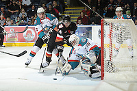 KELOWNA, CANADA, FEBRUARY 17: Jimmy Bubnick #14 of the Calgary Hitmen tries to score on the net of Jordon Cooke #30 of the Kelowna Rockets while being checked by Jesse Lees #2 of the Kelowna Rockets at the Kelowna Rockets on February 17, 2012 at Prospera Place in Kelowna, British Columbia, Canada (Photo by Marissa Baecker/Shoot the Breeze) *** Local Caption ***