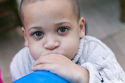 Little boy blowing up a balloon,