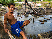 17 JUNE 2016 - DON KHONE, CHAMPASAK, LAOS: A fisherman relaxes on the shore close to fish traps in Khon Pa Soi Waterfalls, on the east side of Don Khon. It's the smaller of the two waterfalls in Don Khon. Fishermen have constructed an elaborate system of rope bridges over the falls they use to get to the fish traps they set. Fishermen in the area are contending with lower yields and smaller fish, threatening their way of life. The Mekong River is one of the most biodiverse and productive rivers on Earth. It is a global hotspot for freshwater fishes: over 1,000 species have been recorded there, second only to the Amazon. The Mekong River is also the most productive inland fishery in the world. The total harvest of fish from the Mekong is approximately 2.5 million metric tons per year. By some estimates the harvest in the Tonle Sap (in Cambodia) had doubled from 1940 to 1995, but the number of people fishing the in the lake has quadrupled, so the harvest per person is cut in half. There is evidence of over fishing in the Mekong - populations of large fish have shrunk and fishermen are bringing in smaller and smaller fish.        PHOTO BY JACK KURTZ