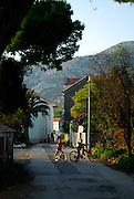 Two boys on bicycles waving, backstreets of Orebic, near Viganj, Croatia