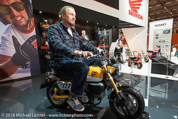 "A 6'-6"" Dmitry Khitrov of the Moscow Custom and Tuning Show checks out a Honda Monkey minibike in the Honda booth at the Intermot International Motorcycle Fair. I don't think this would have made it for his 1,500 mile straight through trip from Moscow, Russia to Cologne, Germany! Thursday October 4, 2018. Photography ©2018 Michael Lichter."