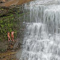 Braving icy water, young women scramble on slippery rocks beside Ouzel Falls, near Big Sky, Montana.