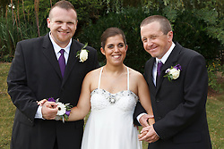Bride who has cerebral palsy, with groom and his father at wedding ceremony.