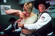 23 FEBRUARY 2002, TUCSON, ARIZONA, USA: Case Drake, a professional bullrider on the Professional Rodeo Cowboys Association (PRCA), left, has an old injury taped up by Rick Foster, of the Justin Sports Medicine Team in the Justin trailer before competing at the Fiesta de los Vaqueros Rodeo in Tucson, Az, Saturday, Feb. 23, 2002. The Justin Sports Medicine Team is sponsored by Justin Boots. They travel to 100 to 150 rodeos per year in the US to provide medical assistance to rodeo competitors. .PHOTO BY JACK KURTZ