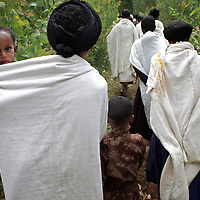 "Women from the village of Mecha on their way to a meeting of the Mecha village Cooperative.<br /> <br /> The Mecha village Cooperative brings together local women beekeepers allowing them to share insights and build a credit union. The Mecha village Cooperative is not yet a member of the Zembaba Union. <br /> <br /> Harvesting honey supplements the income of small farmers in the Ethiopian region of Amhara where there is a long tradition of honey production. However, without the resources to properly invest in production and the continued use of of traditional, low-yielding hives, farmers have not been able to reap proper reward for their labour. <br /> <br /> The formation of the Zembaba Bee Products Development and Marketing Cooperative Union is an attempt to realize the potential of honey production in Amhara and ensure that the benefits reach small producers. <br /> <br /> By providing modern, high-yield hives, protective equipment and training to beekeepers, the Cooperative Union helps increase production and secure a steady supply of honey for which there is growing demand both in and beyond Ethiopia. The collective processing, marketing and distribution of Zembaba's ""Amar"" honey means that profits stay within the cooperative network of 3,500 beekeepers rather than being passed onto brokers and agents. The Union has signed an agreement with the multinational Ambrosia group to supply honey to the export market. <br /> <br /> Zembaba Bee Products Development and Marketing Cooperative Union also provides credit to individual members and trains carpenters in the production of modern hives. <br /> <br /> Photo: Tom Pietrasik<br /> Mecha, Amhara. Ethiopia<br /> November 17th 2010"