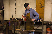 Blacksmith Frank Verga forges red hot steel in a metal working shop in Charleston, SC