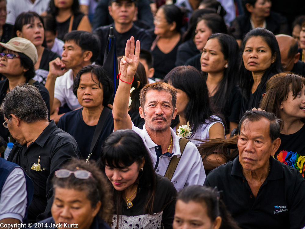 19 OCTOBER 2014 - BANG BUA THONG, NONTHABURI, THAILAND: A man mourning for Apiwan Wiriyachai holds up the now banned three finger saluter from the Hunger Games movies during Apiwan Wiriyachai's cremation at Wat Bang Phai in Bang Bua Thong, a Bangkok suburb, Sunday. The military junta banned the salute after anti-coup activists adapted it to mean opposition to the junta. Apiwan was a prominent Red Shirt leader. He was member of the Pheu Thai Party of former Prime Minister Yingluck Shinawatra, and a member of the Thai parliament and served as Yingluck's Deputy Prime Minister. The military government that deposed the elected government in May, 2014, charged Apiwan with Lese Majeste for allegedly insulting the Thai Monarchy. Rather than face the charges, Apiwan fled Thailand to the Philippines. He died of a lung infection in the Philippines on Oct. 6. The military government gave his family permission to bring him back to Thailand for the funeral. His cremation was the largest Red Shirt gathering since the coup.     PHOTO BY JACK KURTZ