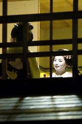 Asia, Japan, Honshu island, Kyoto, Geisha at restaurant in Gion quarter, viewed through window