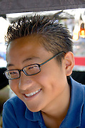 Portrait of happy teen entrepreneur at his concession stand. Hmong Sports Festival McMurray Field St Paul Minnesota USA