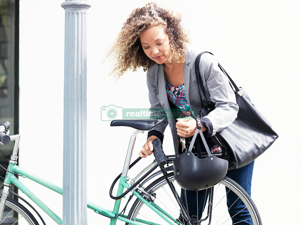 December 3, 2017 - Mid adult woman securing bicycle after journey (Credit Image: © Elke Meitzel/Image Source via ZUMA Press)