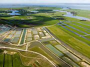 Nederland, Noord-Holland, Amsterdam (landelijk Noord), 16-04-2012; Waterland, overzicht met Volgermeerpolder, daar achter polder Belmermeer en Zuiderwoude, Marken. Rechts het water van de Holysloter Die en het IJsselmeer. Aan de horizon Amsterdam.De Volgermeerpolder maakte oorspronkelijk deel uit van de Veenderij Zunderdorp (midden rechts), waar tot in de jaren '50 turf is gewonnen. Na beeindiging van het vervenen werden de 'petgaten' volgestort met huisvuil en chemisch afval, onder andere met dioxine en benzeen afkomstig van Philips-Duphar..Inmiddels is de polder gesaneerd, de voormalige vuilstortplaats is afgedekt met folie en voorzien van en afdeklagen, bestaande uit zowel grond als ook water. Het ontwerp voorziet in een natuurgebied met 'sawa's' waarin nieuw veen zich kan ontwikkelen wat de vervuilde grond verder zal isoleren (natural capping)..The Volgermeerpolder in the rural area near Amsterdam once a landfill site for heavily polluted household and industrial waste, has been cleaned up using natural capping and turned into a nature area. .luchtfoto (toeslag), aerial photo (additional fee required);.copyright foto/photo Siebe Swart