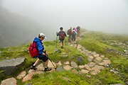Foggy descent from 1637-foot Styhead Pass to Borrowdale valley in Lake District National Park, United Kingdom, Europe. England Coast to Coast hike with Wilderness Travel, day 3 of 14: from Wasdale Head to Seathwaite. From Wasdale Head, we climbed to 1637-foot Styhead Pass, then descended via Styhead Tarn to the valley of Borrowdale. Overnight at Keswick Country House, in Cumbria county. [This image, commissioned by Wilderness Travel, is not available to any other agency providing group travel in the UK, but may otherwise be licensable from Tom Dempsey – please inquire at PhotoSeek.com.] This image was stitched from multiple overlapping photos.