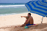 A father points out at the waves as he talks to his little girl, on the beach in Hawaii