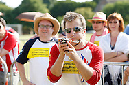 Photo by Andrew Tobin/Tobinators Ltd - 07710 761829 - New 2013 World Champion Rob Bresler takes aim as he wins the final against Toby Bush (background) during the World Peashooting Championships held at Witcham, Cambridgeshire, UK on 13th July 2013. Run in conjunction with the village fair, the Championships have been held in Witcham since 1971 when they were started by a Mr Tyson, the village schoolmaster, in order to raise funds for the village hall.Competitors come from as far afield as the USA and New Zealand to attempt to win the event. The latest technology is often used, including laser sights and titanium and carbon fibre peashooters. All peashooters must conform to strict length rules, not exceeding 12 inches, and have to hit a target 12 feet away. Shooting 5 peas at a plasticine target attached to a hay bale, the highest scorers move through the initial rounds to a knockout competition, followed by a sudden death 10-pea shootout.