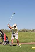 Vertical of golfer swinging at ball