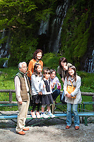 """Japanese Tourists at Shiraito Waterfalls, or """"Falls of White Thread"""" is one of the top 100 waterfalls in Japan, each year earning a different ranking - usually as a result of the quantity of water resulting from snow melts. The falls are located at the Base of Mt Fuji near the town of Fujinomiya"""