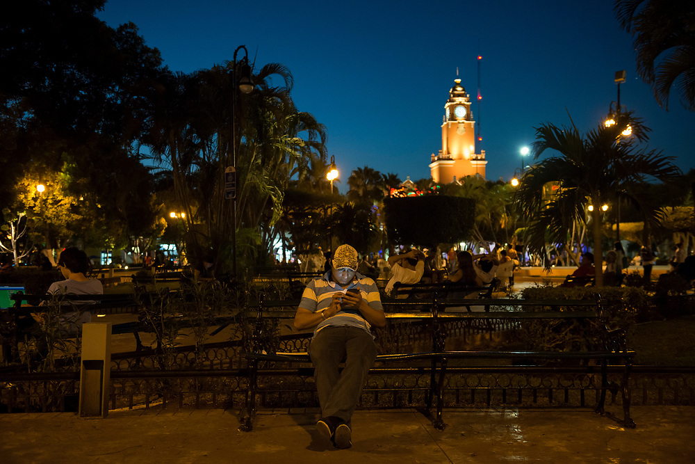 A man sits on a park bench in the Plaza Grande at dusk, looking into his smart phone, in Merida, Mexico