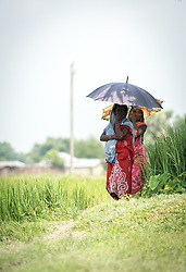 16 September 2018, Sirsiya Tole, Jahada rural municipality, Nepal: Women take cover from the sun under an umbrella in Sirsiya Tole, a community inhabited by Santal and Dalit (Musahar) people, who find themselves as the very margin of society in Nepal. Through support from the Nepal Evangelical Lutheran Church, the community has been able to recover and develop flood resilience, and to mobilize to make their voices heard in the local government, as Nepal is transitioning into a federal government system.