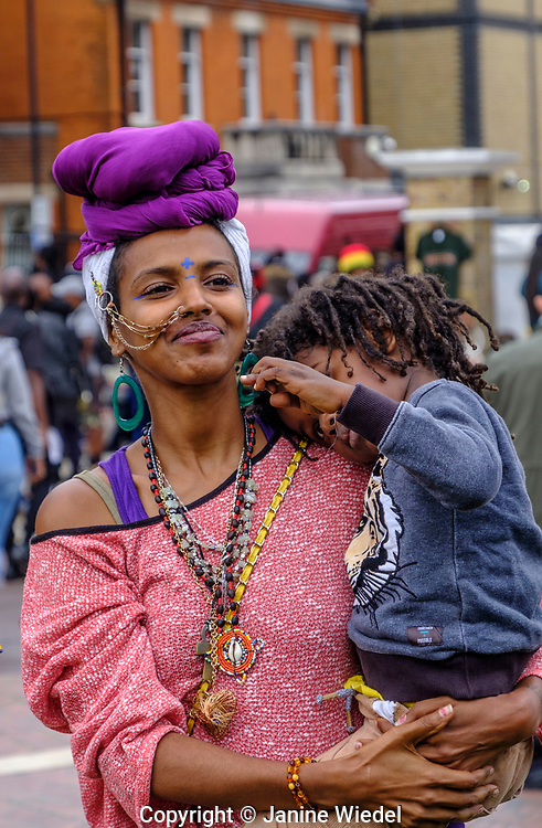 Woman and child with African headwrap at annual Reparation Revolution event on Afrikan Emancipation Day in Windrush Square Brixton 2021.