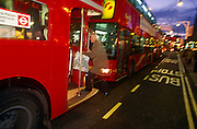 An elderly man leaps onto the rear running board of a traditional Routemaster London bus.