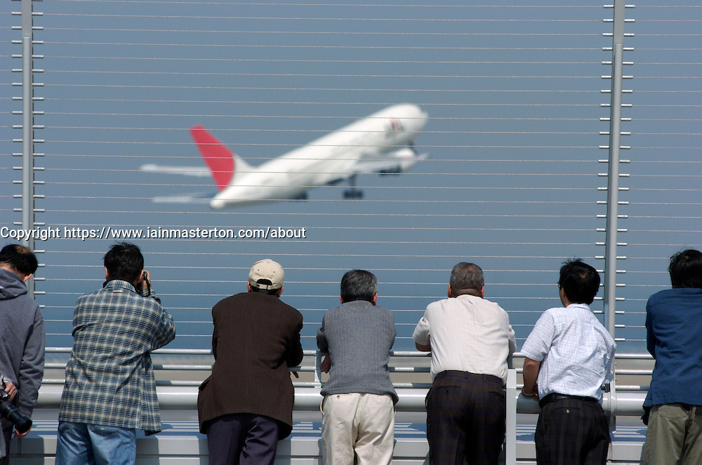 Visitors looking at airline at skydeck viewing platform at Nagoya Airport in Japan