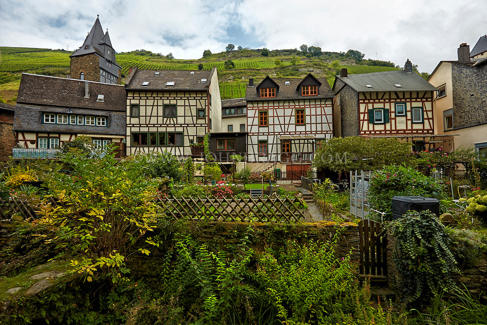 View of half-timbered homes and private gardens, sitting below the vineyards and hills of Bacharach, Germany.
