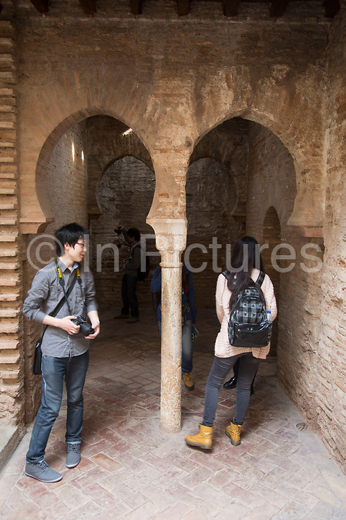 The Alhambra Palace and fortress complex located in Granada, Andalucia, Spain. Chinese tourists in ther Mosque Baths, enjoying the Moorish architecture.