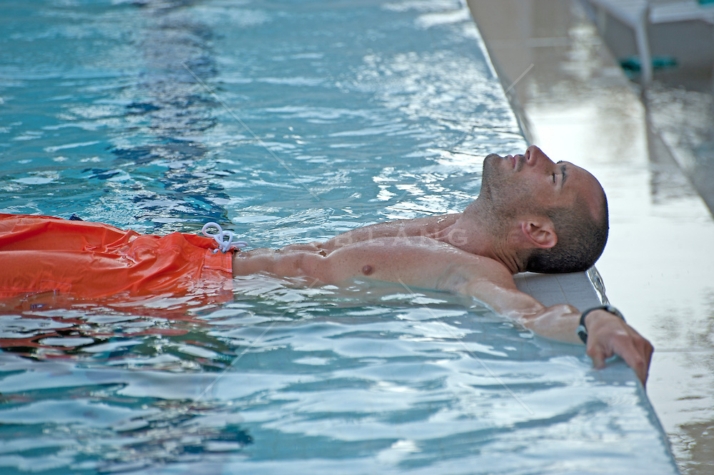 Man taking time out in a pool to float and relax