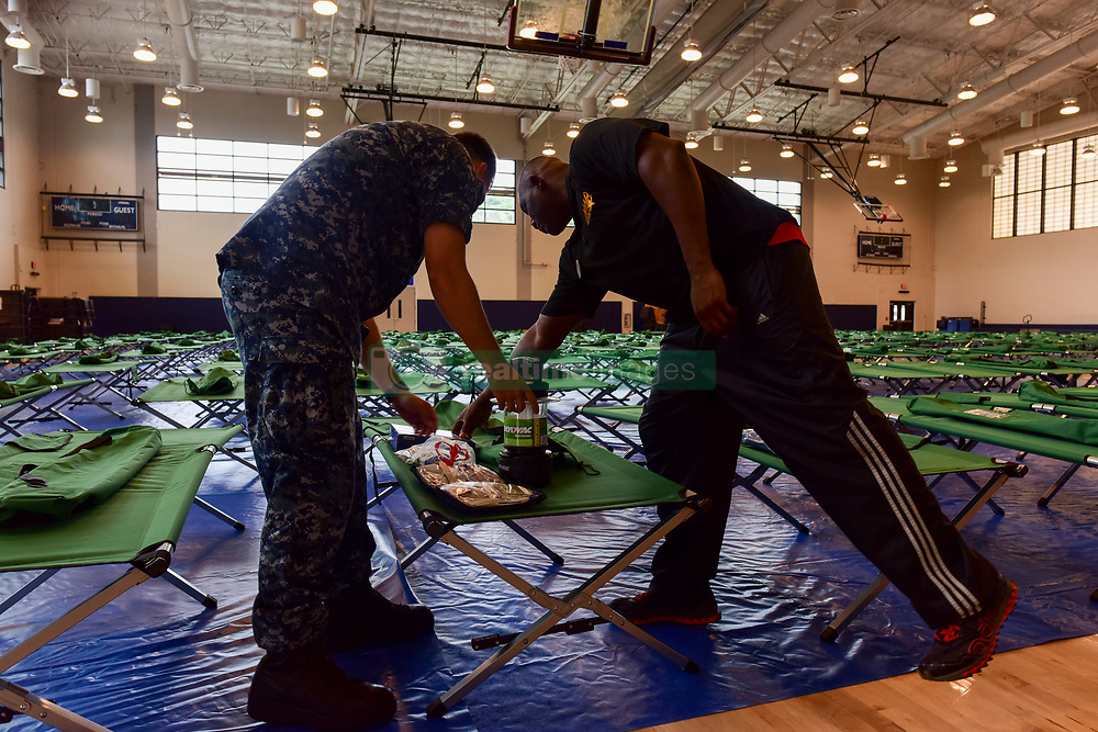 PEARL HARBOR (Aug. 23, 2018) Morale Welfare and Recreation employees and Joint Base Pearl Harbor-Hickam personnel go over emergency preparation kits at the base fitness center as Hurricane Lane approaches Hawaii. In preparation for Category 4 Hurricane Lane, the base is currently at Tropical Cyclone Condition of Readiness (TCCOR) 3, indicating that destructive and sustained winds of 50 knots or greater are possible within 48 hours as of 11 a.m. Hawaii Standard Time. (U.S. Navy photo by Mass Communication Specialist 1st Class Corwin M. Colbert/Released) 180823-N-QE566-003